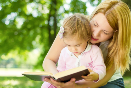 mom holding toddler girl and reading book to her